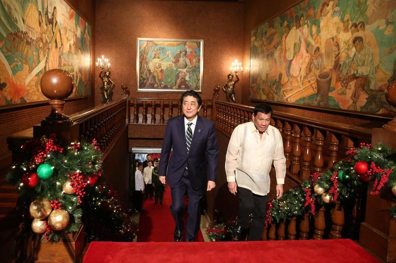 President Rodrigo Duterte (R) walks with Japanese Prime Minister Shinzo Abe as they enter the Malacanang presidential palace in metro Manila, Philippines January 12, 2017. Malacanang Photo/ Handout via Reuters