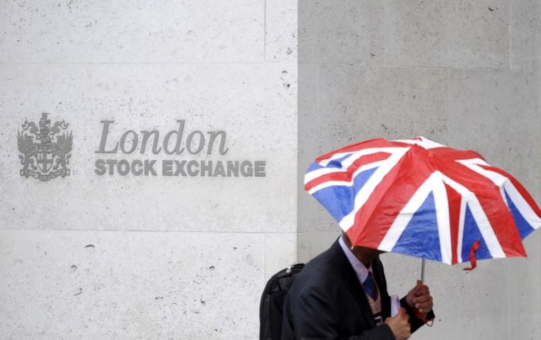 A worker shelters from the rain under a Union Flag umbrella as he passes the London Stock Exchange in London, Britain, October 1, 2008.  REUTERS/Toby Melville/File Photo