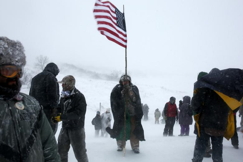 A man holds an American flag while marching with veterans and activists outside the Oceti Sakowin camp where ''water protectors'' continue to demonstrate against plans to pass the Dakota Access pipeline adjacent to the Standing Rock Indian Reservation, near Cannon Ball, North Dakota, U.S., December 5, 2016.  Picture taken December 5, 2016.  REUTERS/Stephen Yang