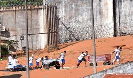 Detentos carregam corpos de mortos após rebelião em presídio no Rio Grande do Norte.    15/01/2017   REUTERS/Josemar Goncalves/