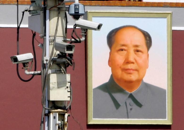 Monitor cameras work in front of the giant portrait of Chairman Mao Zedong on Beijing's Tiananmen Square, September 28, 2009.  REUTERS/Jason Lee/File Photo