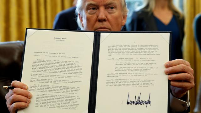 U.S. President Donald Trump holds up a signed executive order to advance construction of the Dakota Access pipeline at the White House in Washington January 24, 2017.  REUTERS/Kevin Lamarque