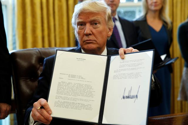 U.S. President Donald Trump holds up a signed executive order to advance construction of the Keystone XL pipeline at the White House in Washington January 24, 2017.  REUTERS/Kevin Lamarque