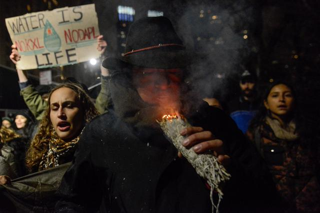 A man burns sage during a protest against President Donald Trump's executive order to allow the Keystone XL and Dakota Access pipelines in New York City, U.S. January 24, 2017. REUTERS/Stephanie Keith