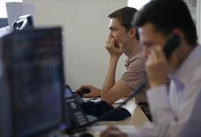 Трейдеры на Московской фондовой бирже. Российские фондовые индексы слегка снизились в среду после бодрой предыдущей сессии, а лучше рынка по-прежнему выглядят низколиквидные бумаги алюминиевого гиганта Русала, который готовится к размещению еврооблигаций. REUTERS/Sergei Karpukhin