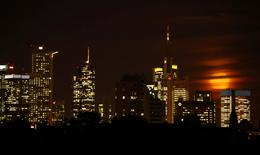 FILE PHOTO - The moon is partly covered by clouds as it rises above the skyline of Frankfurt, Germany, early evening November 14, 2016. REUTERS/Kai Pfaffenbach/File Photo