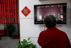 """Инвестор смотрит на электронное табло с данными о торгах. Китайские фондовые индексы повысились по итогам торгов четверга пятый день подряд, при этом индекс """"голубых фишек"""" закрылся на новом шестинедельном максимуме, но подъем котировок ограничили данные о том, что темпы роста прибылей промышленных компаний сильно замедлились в прошлом месяце. REUTERS/Aly Song"""