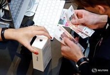 Покупатель расплачивается за iPhone 7 в Москве 23 сентября 2016 года. Apple Inc впервые за пять лет вернула себе звание крупнейшего мирового продавца смартфонов, обойдя ближайшего конкурента Samsung по числу проданных за праздничный квартал аппаратов, и нарастила выручку благодаря успеху флагмана iPhone 7 Plus. REUTERS/Sergei Karpukhin