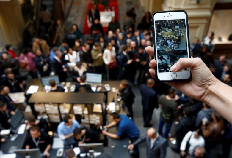 A visitor takes pictures as customers gather at a store selling Apple products during the launch of the new iPhone 7 sales at the State Department Store, GUM, in central Moscow, Russia September 23, 2016. REUTERS/Sergei Karpukhin
