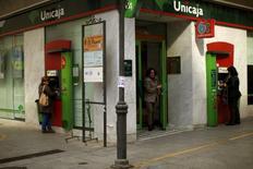 El grupo bancario Unicaja redujo su beneficio atribuido en 2016 un 24 por ciento a 142 millones de euros, después de provisionar 130 millones por el posible impacto de la sentencia europea sobre las cláusulas suelo consideradas abusivas. En esta imagen de archivo, unas mujeres utilizan unos cajeros en una sucursal de Unicaja en la localidad malagueña de Ronda, el 29 de enero de 2014. REUTERS/Jon Nazca