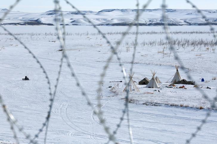An opponent of the Dakota Access oil pipeline is seen through concertina wire while snowmobiling toward the protest camp near Cannon Ball, North Dakota, U.S., January 29, 2017. REUTERS/Terray Sylvester