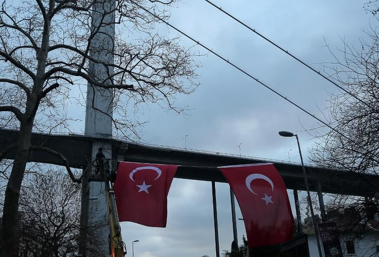 A worker attaches Turkish flags near the Reina nightclub by the Bosphorus, which was attacked by a gunman, in Istanbul, Turkey, January 1, 2017. REUTERS/Huseyin Aldemir
