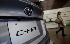 Una mujer pasa por delante del modelo C-HR de Toyota Motor Corp que se exhibe en su sede de Tokio, Japón. 6 de febrero 2017. Toyota Motor Corp reportó el lunes una caída en sus ganancias operativas trimestrales, aunque aumentó en un 9,7 por ciento sus previsiones de utilidades para todo el año. REUTERS/Kim Kyung-Hoon