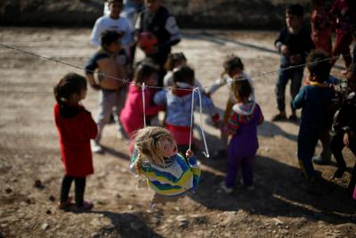 Barbed wire swings and cardboard sleds in Iraqi camp