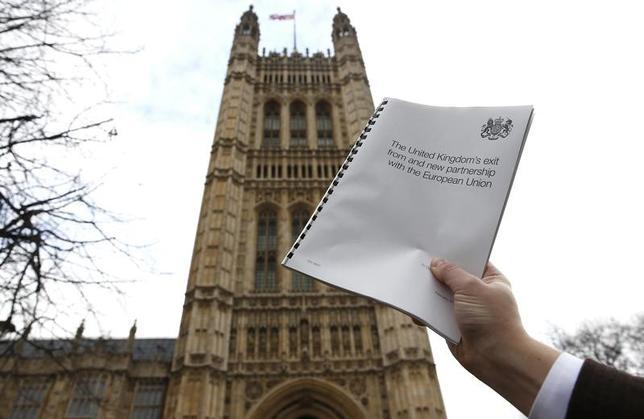 2月6日、英議会は、EUに離脱を通知する権限をメイ首相に与える法案について審議を行い、親EU派議員が提出した一連の修正法案を否決した。写真は英国政府が公表した離脱手続き開始に発動するEU基本条約(リスボン条約)50条関連法案のコピー。ロンドンの国会議事堂を背景に2日撮影(2017年 ロイター/Peter Nicholls)