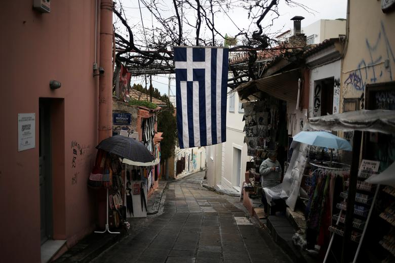 A Greek national flag hangs outside a shop during a rainy day at the Plaka district, in Athens, Greece, January 24, 2017. REUTERS/Alkis Konstantinidis