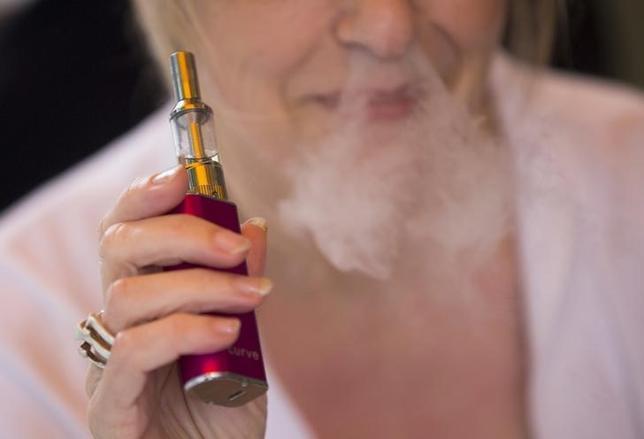 2月7日、ロンドン大学が主導して行われた研究で、電子たばこの使用は従来のたばこに比べはるかに安全で、毒性が少ないことが分かった。写真は電子たばこを吸う女性、2015年8月ロンドンで撮影(2017年 ロイター/Neil Hall)