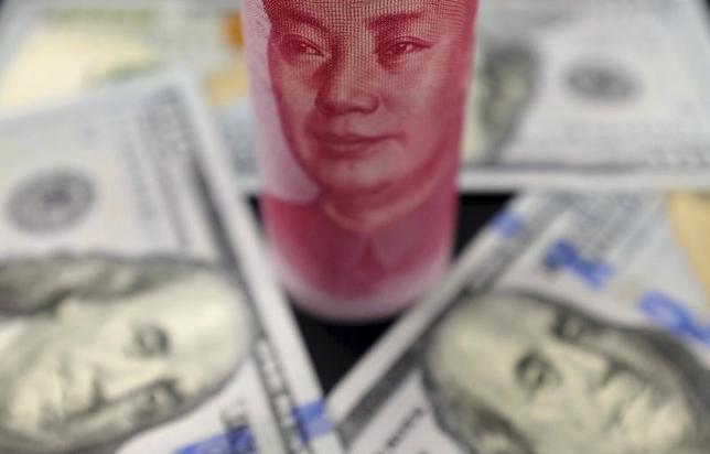 2月8日、中国の外貨準備高は、憂慮すべき譲れない一線を越えたと言える。写真は人民元とドル紙幣。北京で昨年1月撮影(2017年 ロイター/Jason Lee)