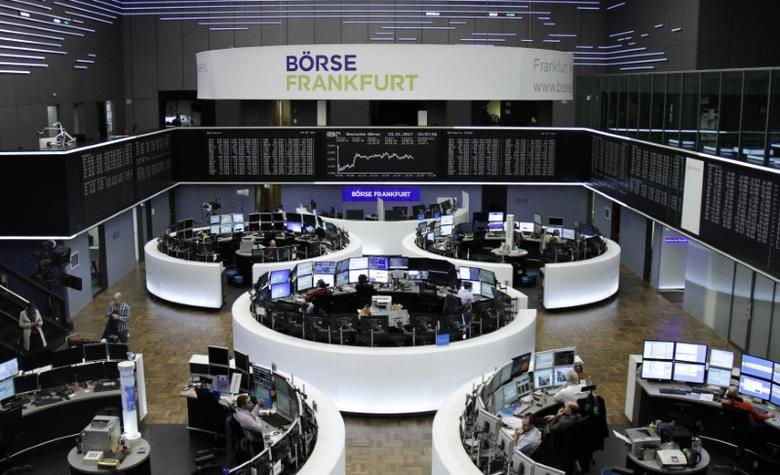 Traders work at their desks in front of the German share price index, DAX board, at the stock exchange in Frankfurt, Germany, January 23, 2017. REUTERS/Staff/Remote