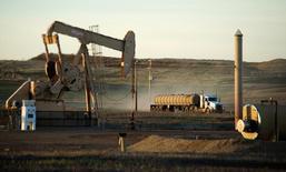 Imagen de archivo en la que se ve un camión cisterna pasando junto a un pozo de petróleo en la reserva india Fort Berthold en Dakota del Norte, el 1 de noviembre de 2014.Los precios del petróleo caían el miércoles y extendían los  descensos de la sesión anterior, ya que un gran aumento en los inventarios de Estados Unidos y una menor demanda china sugerían que los mercados de crudo siguen sobreabastecidos pese a los esfuerzos de la OPEP por reducir la producción. REUTERS/Andrew Cullen