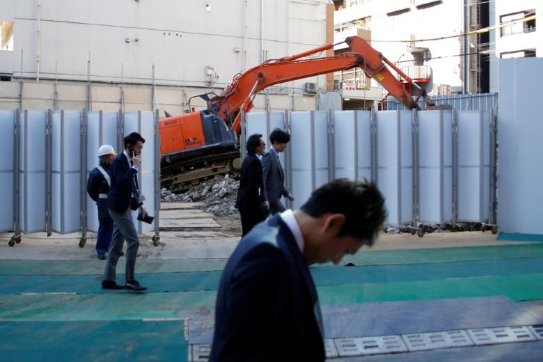 Businessmen walk past heavy machinery at a construction site in Tokyo's business district, Japan, January 16, 2017.    REUTERS/Toru Hanai