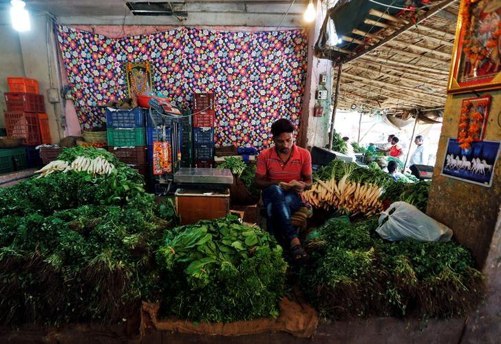 A vegetable vendor counts Indian currency notes as he waits for customers at a wholesale vegetable market in Ahmedabad, India, December 14, 2016. REUTERS/Amit Dave/Files