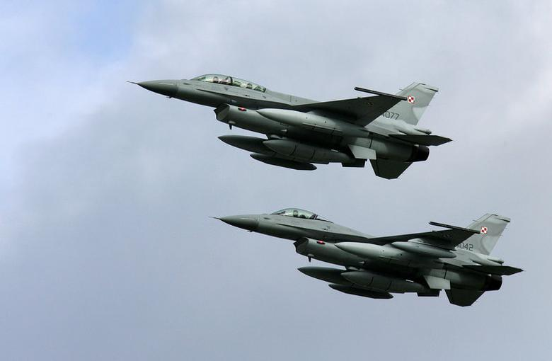 FILE PHOTO -  Two of the first four Polish Air Force F-16 fighter jets arrive at the Krzesiny airport in western Poland, near the city of Poznan November 9, 2006. To match Exclusive AIRSHOW-INDIA/LOCKHEED   REUTERS/Peter Andrews/File Photo