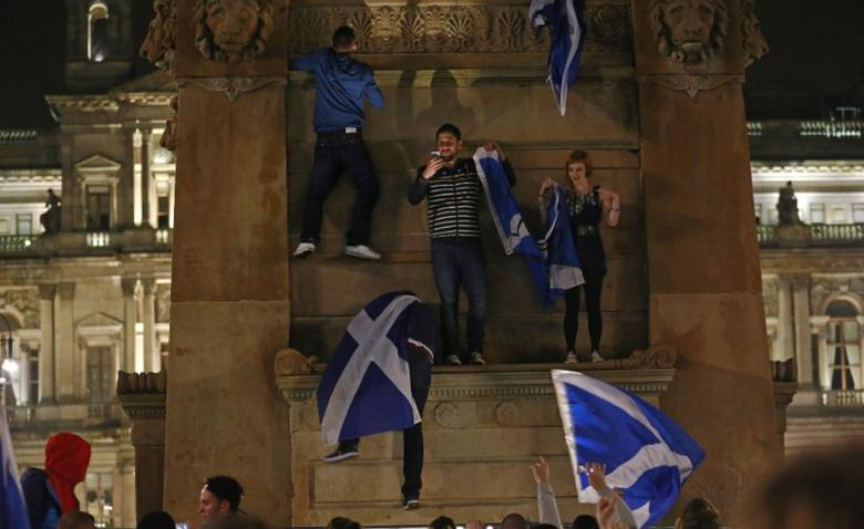People waving Scottish Saltire flags climb onto the Scott Monument in central Glasgow September 18, 2014. REUTERS/Cathal McNaughton