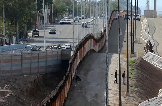Three men from India jump the fence from Mexico and give themselves up to U.S. border patrol agents in Calexico, California, U.S. February 8, 2017. REUTERS/Mike Blake