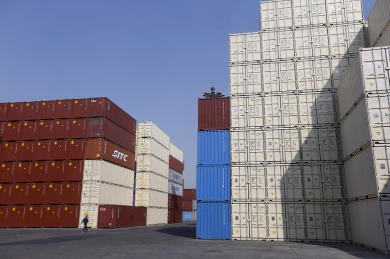A man walks past containers at a port in Shanghai, China, February 17, 2016. REUTERS/Aly Song/File Photo