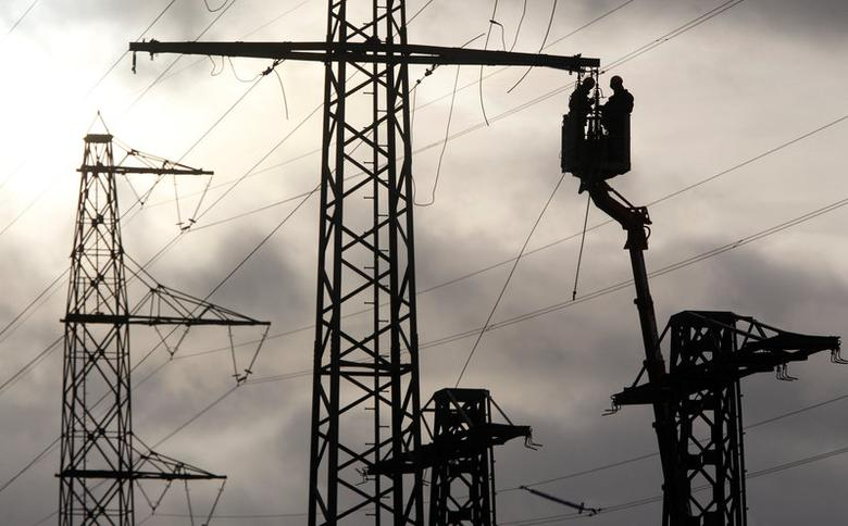 FILE PHOTO: Workers are silhouetted as they remove parts of a power pole to rebuild power lines in the western city of Meckenheim January 30, 2013. REUTERS/Ina Fassbender/File Photo