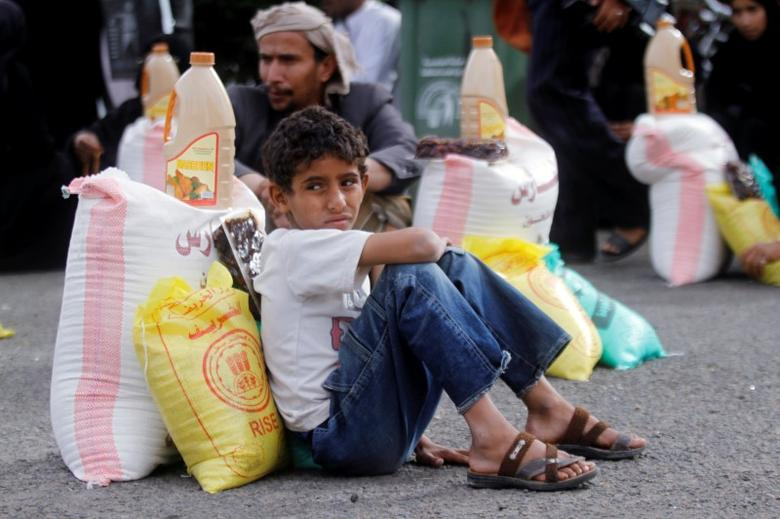 A boy sits next to food supplies he received from a local charity in Sanaa, Yemen, June 23, 2016. REUTERS/Mohamed al-Sayaghi