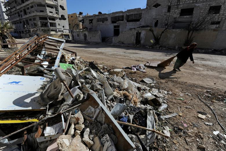 A woman walks past debris along a street in Aleppo's Belleramoun Industrial Zone, Syria February 2, 2017. Picture taken February 2, 2017. REUTERS/Omar Sanadiki