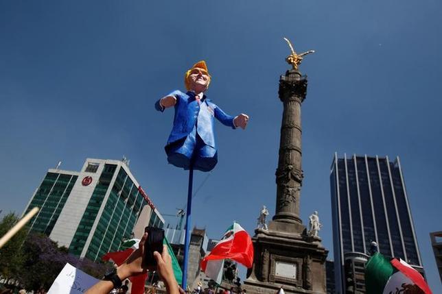 2月11日、トランプ米大統領はツイッターで、メキシコとの国境沿いに建設する壁の費用を引き下げると表明した。壁建設に反対するデモでトランプ氏を模した人形を掲げる男性、メキシコ市で12日撮影(2017年 ロイターJose Luis Gonzalez)