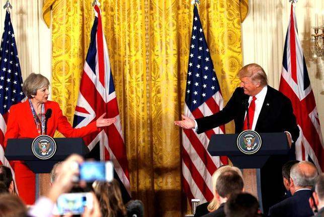 2月10日、メイ英首相(写真左)がトランプ米大統領(写真右)に公式訪問を要請したことを受けて、英国では、公式訪問に反対する抗議の声が広がっているが、最新の世論調査によると、公式訪問に「問題はない」と回答が多数派を占めた。写真はワシントンにあるホワイトハウスで1月に行われた共同記者会見。(2017年 ロイター/Kevin Lamarque)