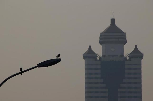 2月14日、北京市は大気汚染対策の一環として、15日から一定の排出基準を満たさない自動車を規制する。新華社が北京市政府の話として伝えた。写真はスモッグで曇る北京。3日撮影(2017年 ロイター/Jason Lee)