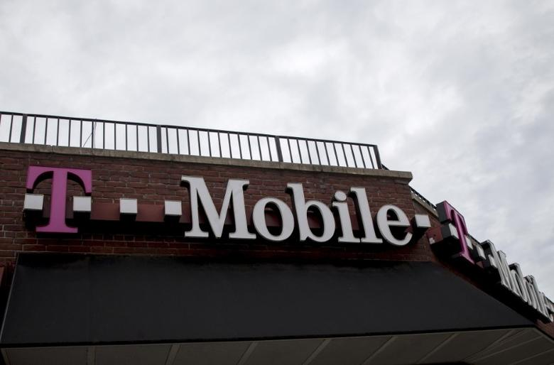 People pass by a T-Mobile store in the Brooklyn borough of New York June 4, 2015.  REUTERS/Brendan McDermid