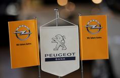 El logo de Opel, filial de General Motors junto al logo de Peugeot se pueden ver en Leverkusen, Alemania. 22 de octubre 2012. General Motors  y PSA Group están en discusiones avanzadas para fusionar al fabricante de automóviles francés con Opel, negocio europeo de GM, dijeron el martes a Reuters dos fuentes con conocimiento del tema.   REUTERS/Wolfgang Rattay/File Photo