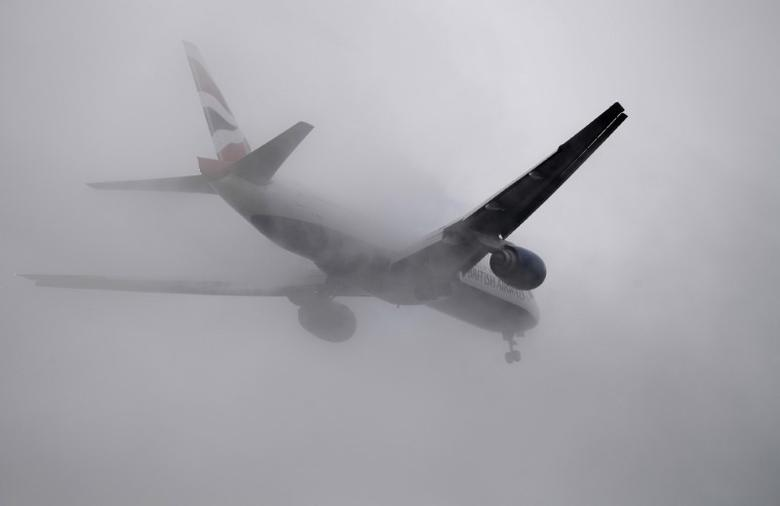 A British Airways passenger aircraft flies through low cloud as it prepares to land at Heathrow airport in west London, Britain, January 7, 2017. REUTERS/Toby Melville