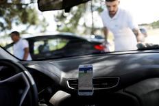Un conductor de Uber limpia su auto mientras su teléfono celular muestra la fila para recoger pasajeros que salen del Aeropuerto Internacional de Guarulhos en Sao Paulo, Brasil, 13 de febrero de 2017. REUTERS/Nacho Doce