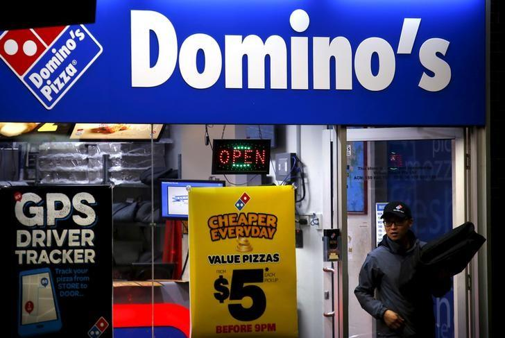 A worker carries a pizza for delivery as he exits a Domino's pizza store in Sydney, Australia, August 12, 2015.   REUTERS/David Gray/Files