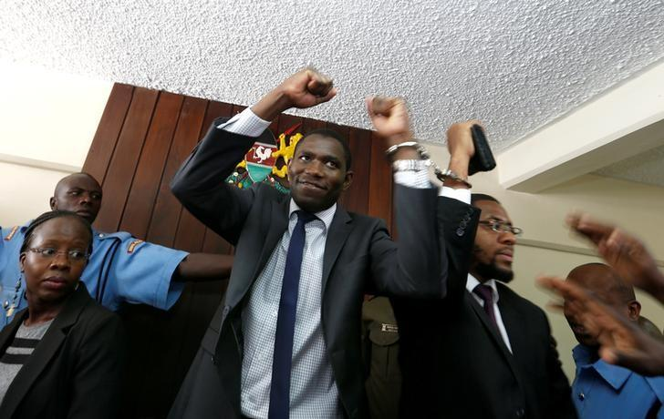 A policeman leads the handcuffed officials of the Kenya Medical Practitioners, Pharmacists and Dentist Union (KMPDU), after their case to demand fulfilment of a 2013 agreement between their union and the government that would raise their pay and improve working conditions at the employment and labour relations courts in Nairobi, Kenya, February 13, 2017. REUTERS/Thomas Mukoya