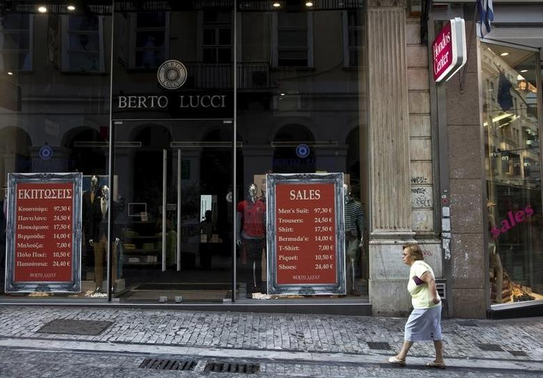 A woman makes her way at a main commercial street in the early morning before the shops were open in central Athens, Greece July 28, 2015.   REUTERS/Ronen Zvulun