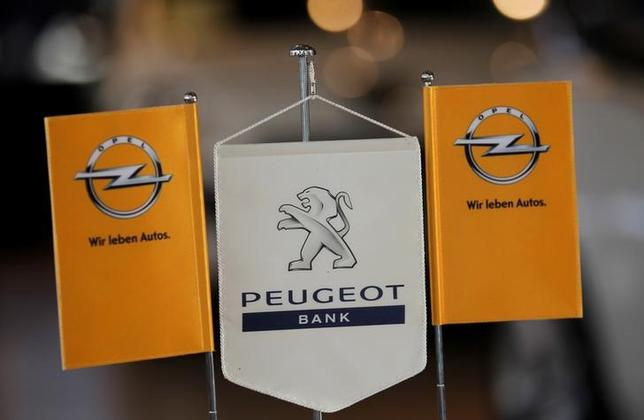 FILE PHOTO: The logo of German General Motors daughter Opel and the bank of French car maker Peugeot are seen at a Opel and Peugeot dealership in Leverkusen near Cologne October 22, 2012.    REUTERS/Wolfgang Rattay/File Photo