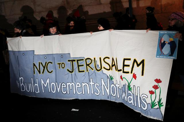 Demonstrators hold a banner during a ''Muslim and Jewish Solidarity'' protest against the policies of U.S. President Donald Trump and Israeli Prime Minister Benjamin Netanyahu at Grand Central Terminal in New York City, U.S., February 15, 2017. REUTERS/Mike Segar