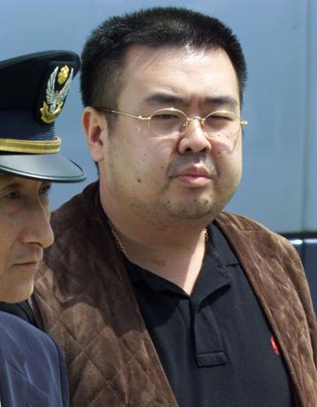 FILE PHOTO: North Korean heir-apparent Kim Jong Nam (R) is escorted by police as he boards a plane upon his deportation from Japan at Tokyo's Narita international airport May 4, 2001.   REUTERS/Eriko Sugita/File Photo