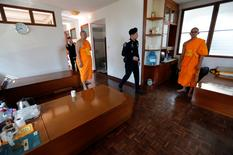 A policeman and Buddhist monks search for a fugitive Buddhist monk inside Dhammakaya temple in Pathum Thani province, Thailand February 17, 2017. REUTERS/Chaiwat Subprasom