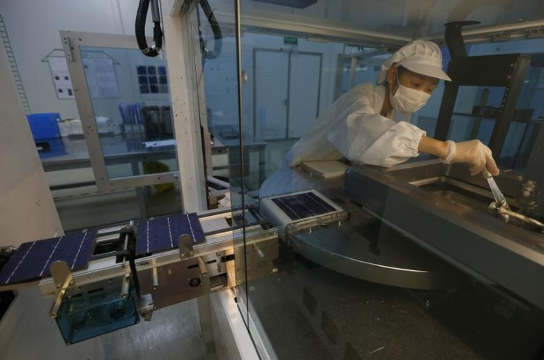 An employee works on a production line of solar panel at a factory of a photovoltaic company in Jiaxing, Zhejiang province June 5, 2013.  REUTERS/William Hong