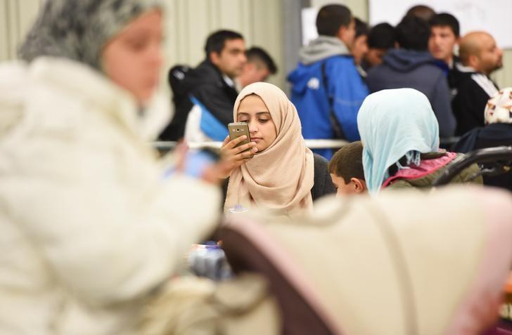 A migrant uses her cell phone in a canteen in a refugee camp in Celle, Lower-Saxony, Germany October 15, 2015.  REUTERS/Fabian Bimmer/Files