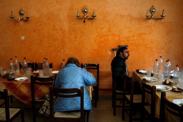 教会が運営する給食施設で食事をとる人々(2017年 ロイター/Alkis Konstantinidis)